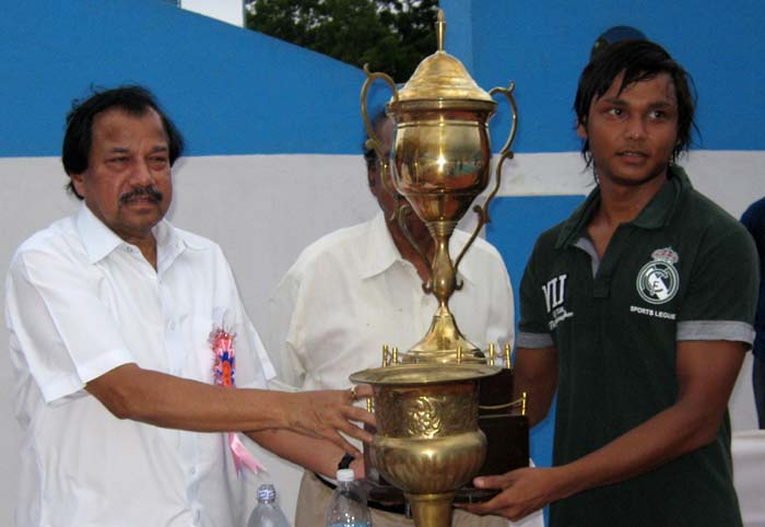 Chintan Naik (R), the best men`s swimmer of the 51st State championship receives the trophy from OOA secretary Asirbad Behera in Bhubaneswar on June 7, 2010.