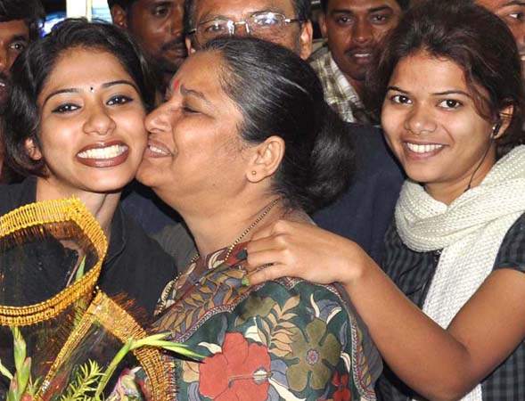 Woman karateka Valena Valentina (Left) gets a kiss from her mother while her sister looks on in Bhubaneswar.