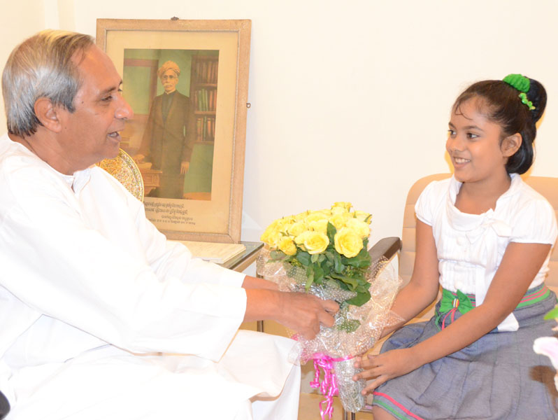 Chief Minister Naveen Patnaik felicitates youngest Odisha Woman Candidate Master Saina Salonika in Bhubaneswar on May 17, 2012.