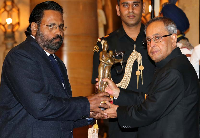 Rowing coach Jose Jacob receives the Dronacharya Award from President Pranab Mukherjee in New Delhi on August 29, 2014.