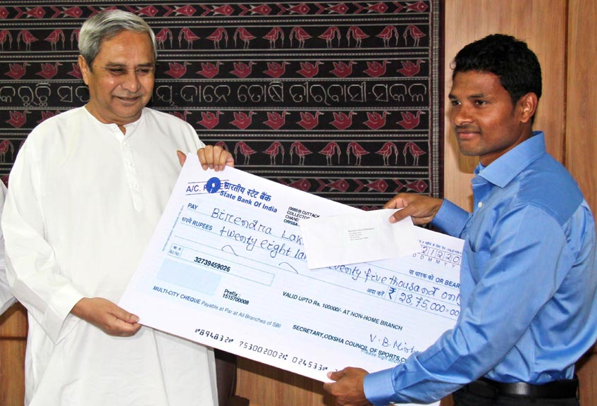 Hockey international Birendra Lakra receives cash award from Chief Minister Naveen Patnaik in Bhubaneswar on December 4, 2014.