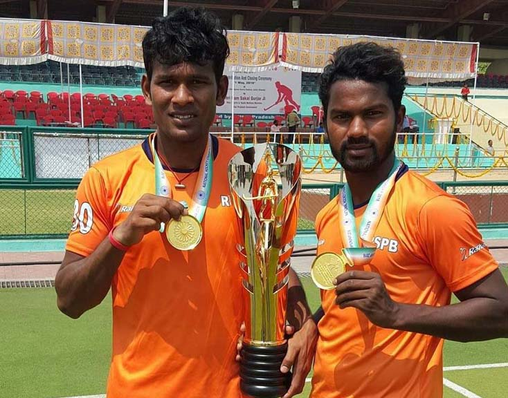 Odisha duo Amit Rohidas and Stanli Victor Minz display the trophy after helping Indian Railways win the title in the 6th Hockey India Senior Men National Championship (Division-A) at Saifai (UP) on May 1, 2016.