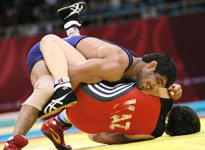 Indian wrestler Sushil Kumar tries to pin an opponent in Beijing Olympics on August, 2008.