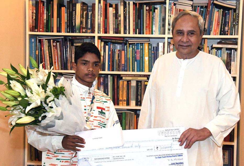 Chief Minister Naveen Patnaik presents Wushu World Junior silver medallist Babulu Munda with a cheque of Rs 2.33 lakhs in Bhubaneswar on July 30, 2018.