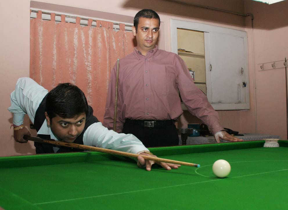 Siddharth Sen (Left) aims for a putt while opponent Mehul Rathor waits for his turn in the opening senior match of the State Billiards Championship in Bhubaneswar on September 26, 2008.