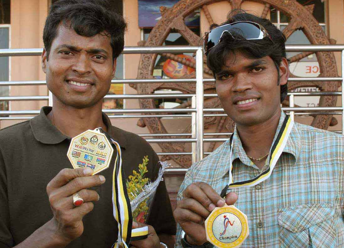 Dilip Tirkey (Left) and Prabodh Tirkey display their Azlan Shah Cup medals on their return home in Bhubaneswar on April 14, 2009.